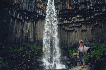 Beautiful landscape of Iceland. Girl looking on waterfall
