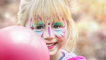 Glückliches geschminktes Mädchen beim Kinderkarneval auf einem Freizeitpark mit einem pinken Luftballon