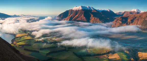 The valley is flooded in mist in a mountain environment. Over the fogs, only the high peaks of the mountains rise beneath the sunny sky. Misty morning on the Southern Island New Zealand, Christchurch