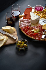 Antipasti board with cheese and meat snacks with red wine and baguette on board on black table