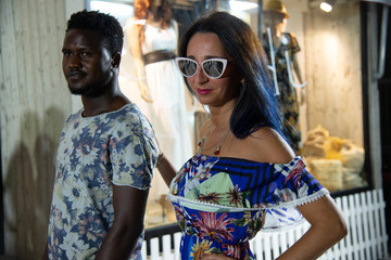 Portrait of happy interracial amorous couple. African man looking at his Caucasian woman. Elegant young couple while strolling through the city. The girl wears sunglasses and puts a hand on the boy's