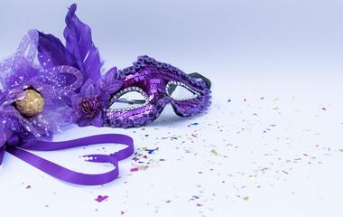 Violet masks on white background and violet flower and ribbon heart shape. Carnival or Carnival Sunday concept.