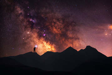A beautiful starry night, a silhouette of a man, stands on a mountain and looks at the Milky Way galaxy.