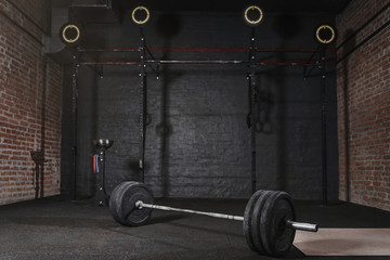 Crossfit athlete lifting barbell overhead at the gym. Shirtless man doing functional training. Practicing powerlifting.