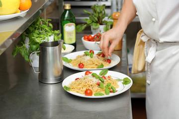 Kucharz przygotowuje spaghetti na białych talerzach.