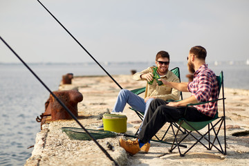 leisure and people concept - happy friends fishing and drinking beer on pier in summer