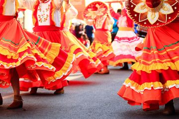 a group of mexican women dancing with bright handmade mexican dresses during mexican carnival
