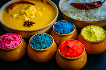 Holi indian festival of colors. Food with colours, steam rice, panir butter masala, pepper chilie, starnise. Powder colours arranged over black background. Selective focus