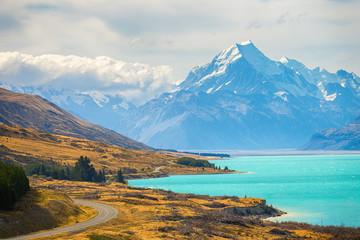 Wspina się kucbarskiego punkt widokowy z jeziornym pukaki i drogę prowadzącą wspinać się wioskę kucharską inewpoint z jeziornym pukaki i drogą prowadzącą wspinać się wioskę kucharską w Południowej wyspie Nowa Zelandia.