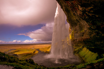 View of a waterfall in Iceland. Water flows from top to bottom.