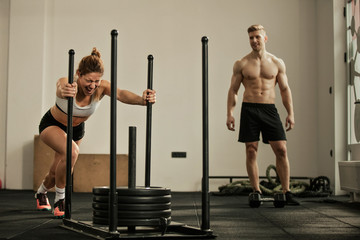 Athletic woman making effort while pushing gym sled with weights on cross training.