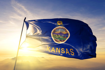 Kansas state of United States flag waving on the top sunrise mist fog
