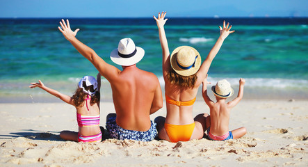happy family father, mother and children backs on  beach at sea.