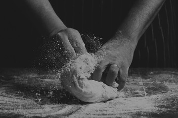 Man with apron kneading a ball of dough on wooden board by hand in artistic conversion