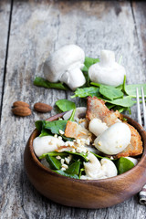 Healthy mushroom salad with spinach and bacon on wooden table