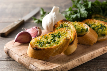 Garlic breads slice and ingredients on wooden table.
