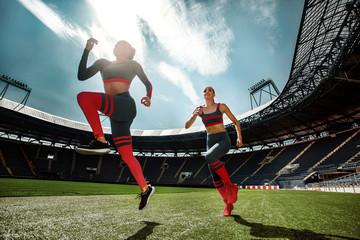 Strong athletic woman sprinter, running on stadium wearing in sportswear. Fitness and sport motivation. Runner concept.