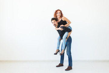 People and love concept - Beautiful pretty woman sitting at man's back and embracing him on white background with copy space
