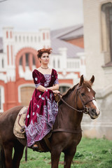 a girl in classical dress pats his horse on the background of the castle