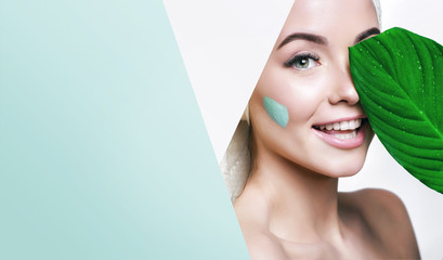 Portrait of beautiful woman with healthy glow perfect smooth skin holds tropical leaf, look into the hole of green paper. Young girl enjoys cream facial mask. Fashion, beauty, skincare concept.