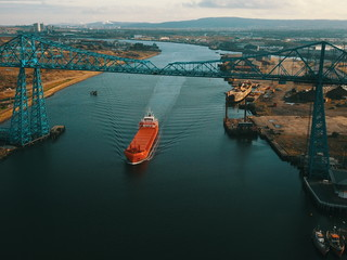 The river tees at Middlesbrough showing a large ship passing down the tees near the iconic transporter bridge