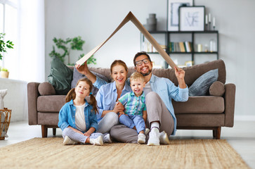 concept of housing and relocation. happy family mother father and kids with roof at home .