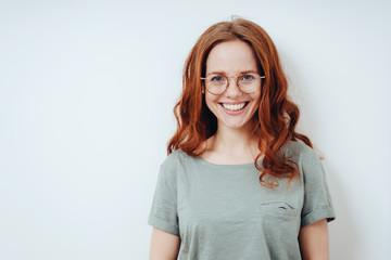 Happy vivacious young redhead woman