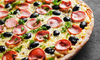 Pizza with Mozzarella cheese, olives, ham, tomato sauce, sausage, pepper, Spices. Italian pizza Italian pizza on wooden table background