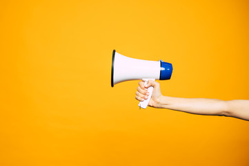 In a bull voice. A yellow background with a woman's hand in front of it holding three colored  megaphone of white, black and blue colors.