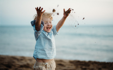 A small toddler boy standing on beach on summer holiday, throwing sand.