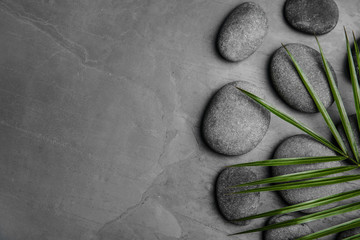 Zen stones and tropical leaf on dark background, top view with space for text