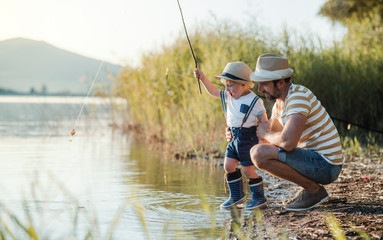 A mature father with a small toddler son outdoors fishing by a lake.