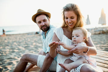 A family with a toddler girl sitting on sand beach on summer holiday.