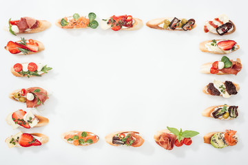 top view of frame made of traditional italian bruschetta with prosciutto, salmon, fruits, vegetables and herbs on white with copy space