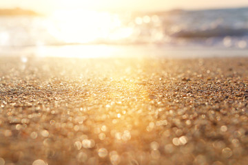 background image of sandy beach and ocean waves with bright bokeh lights
