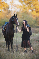 Smiling woman in black dress standing near the horse and holding the rains