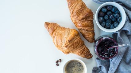 Croissant z owocami i kawą leżące na białym tle