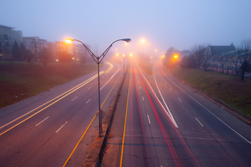 Highway at foggy night with bright trails of light from incoming and outgoing traffic.