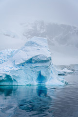 Sculptural blue iceberg, with reflection in the sea, against a foggy mountain background, Danco Island, Antarctica