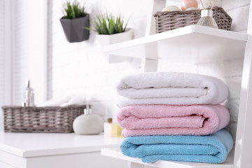 Stack of fresh towels on shelf in bathroom. Space for text