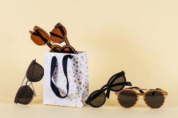 Sunglasses sale concept. Different sunglasses in shoping bags on yellow background. Fashion summer accessories. Copy space