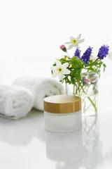 handtücher neben einer Cremedose vor weißem Hintergrund und Blumen in einer Vase.