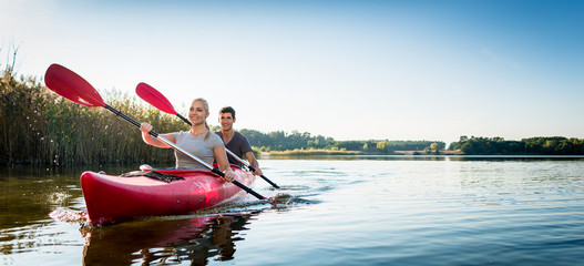 Beautiful couple sailing kayak on lake
