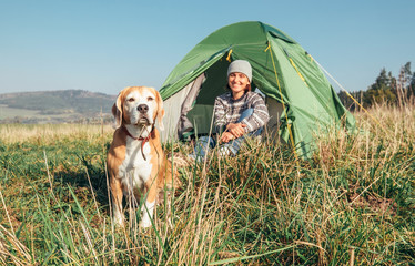 Woman with her pet beagle dog rest in camping tent