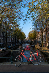Red bicycle parking on the bridge over the calm water of a canal with a boat giving a round trip to tourists, Amsterdam, Netherlands