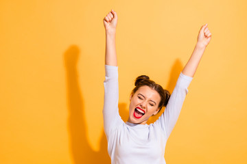 Portrait of her she nice-looking attractive lovely winsome sweet cheerful cheery optimistic girl having fun rejoicing raising hands up party isolated on bright vivid shine yellow background