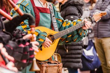 Średniowieczny trubadur grający na gitarze antycznej.