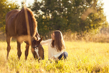 Young girl with horse in field