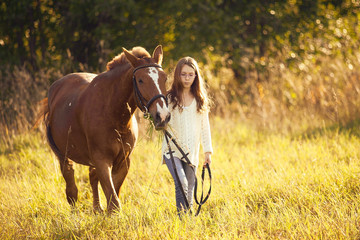 Young girl with sorrel horse in field