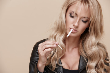 Portrait of a young beautiful blonde woman. Girl lights a cigarette